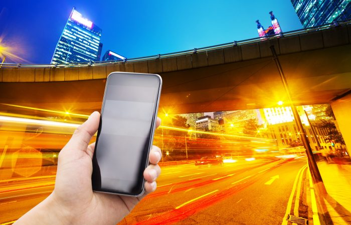hand met telefoon en drukke straat op achtergrond